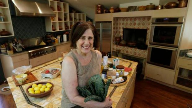 This photo taken Friday, May 30, 2014, shows cookbook author Paula Wolfert with a bunch of kale at her home in Sonoma, Calif. Wolfert spent more than 50 years researching and writing about food. Now, she's enlisting food as an ally in a fight to stay mentally sharp. (AP Photo/Rich Pedroncelli)